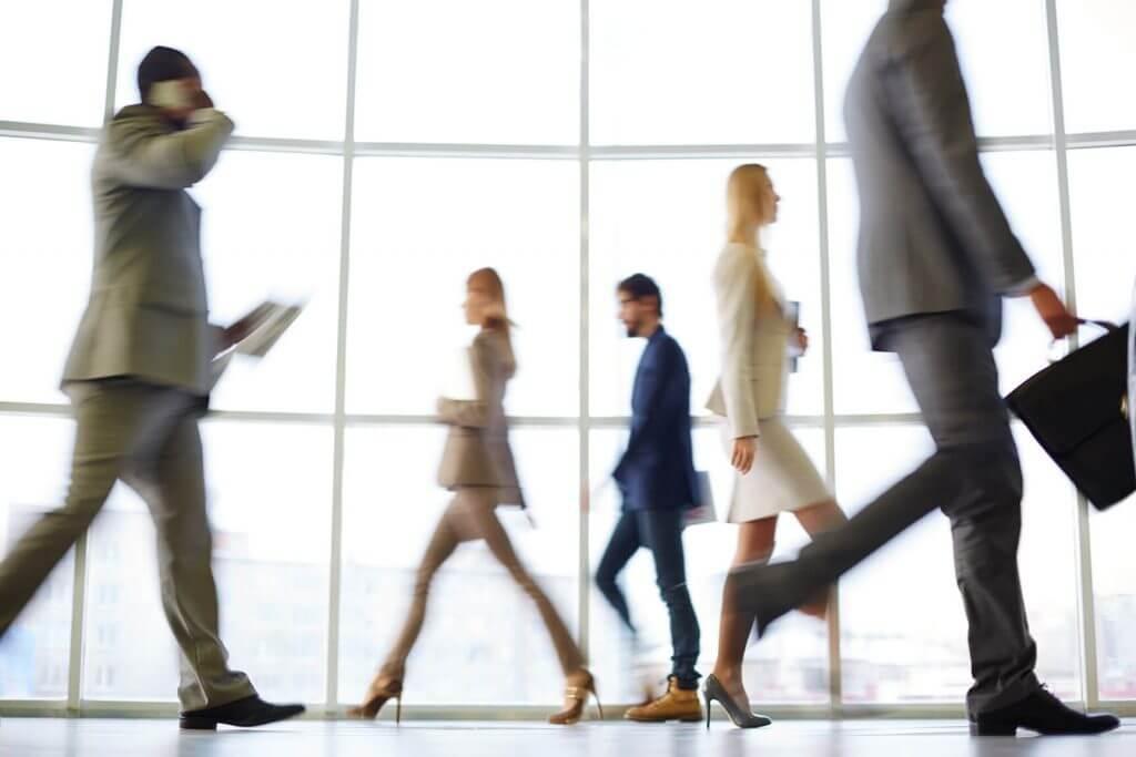 Businessmen and women walking briskly through a hallway
